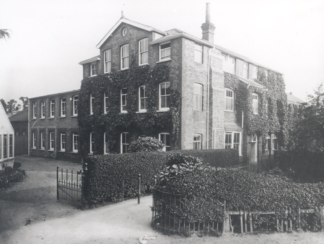 Black and white photograph of exterior view of the Claudius Ash Sons & Co. Ltd. works in Churchfield Road, Walton, showing ivy clad building behind neatly clipped hedge, c.1914.