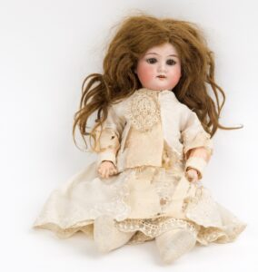 Victorian bisque doll with brown hair, china head and hands, c.1889.Victorian bisque doll with brown hair, china head and hands, c.1889.