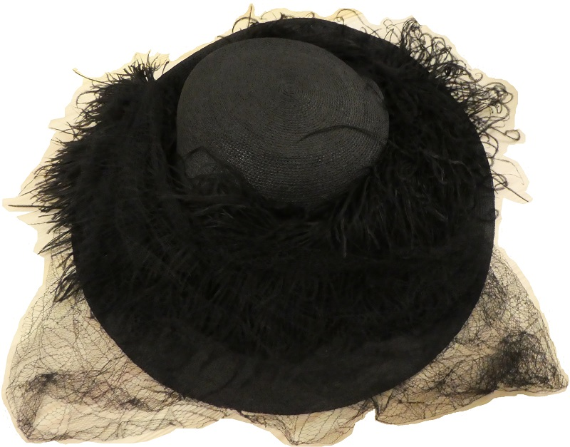 Hat made of silk-lined straw and is trimmed with black net and feathers. It was worn at 'Black Ascot', which was an event that commemorated the death of King Edward VII in May 1910.