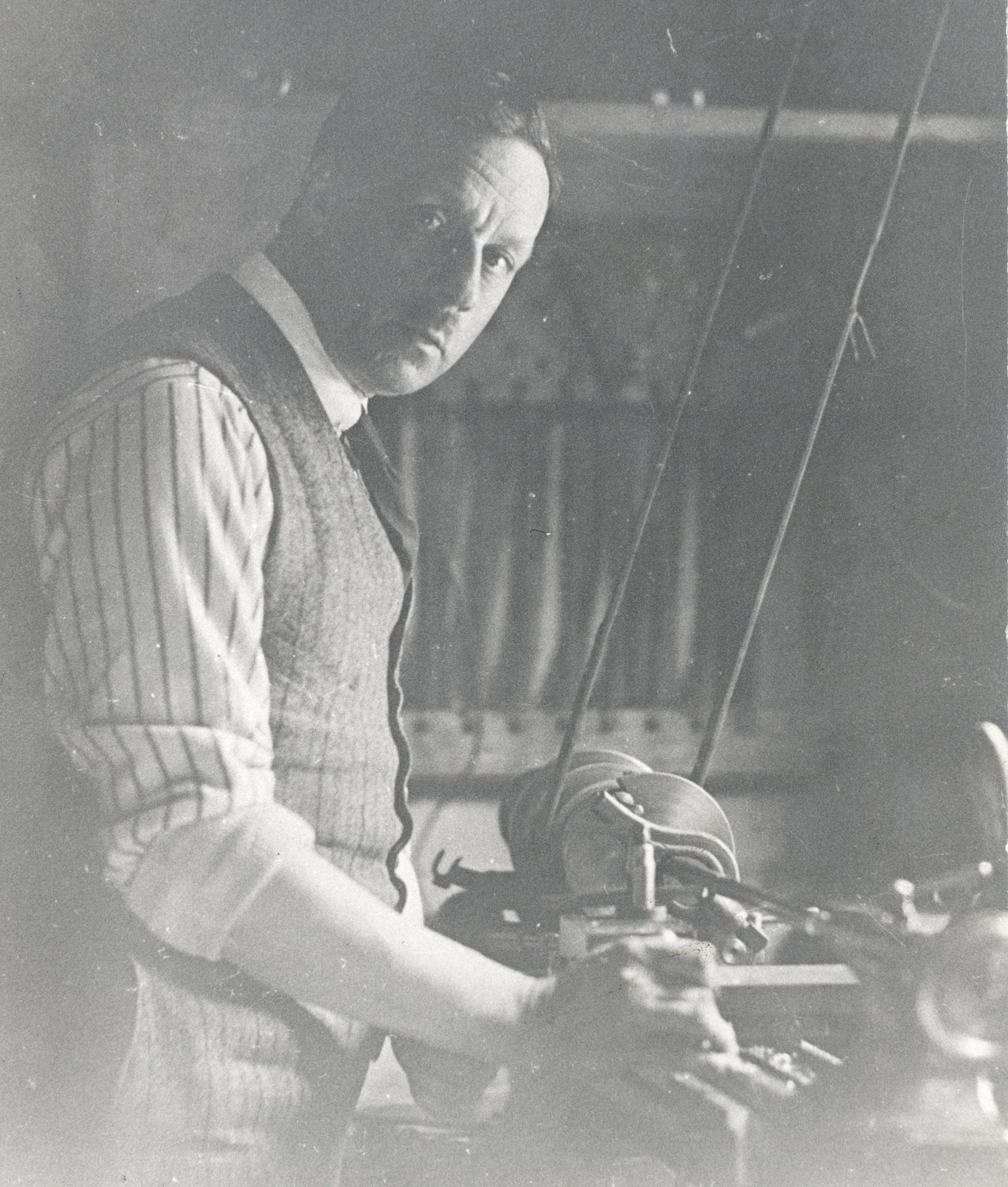 Cecil Hepworth standing by a dynamo apparatus.