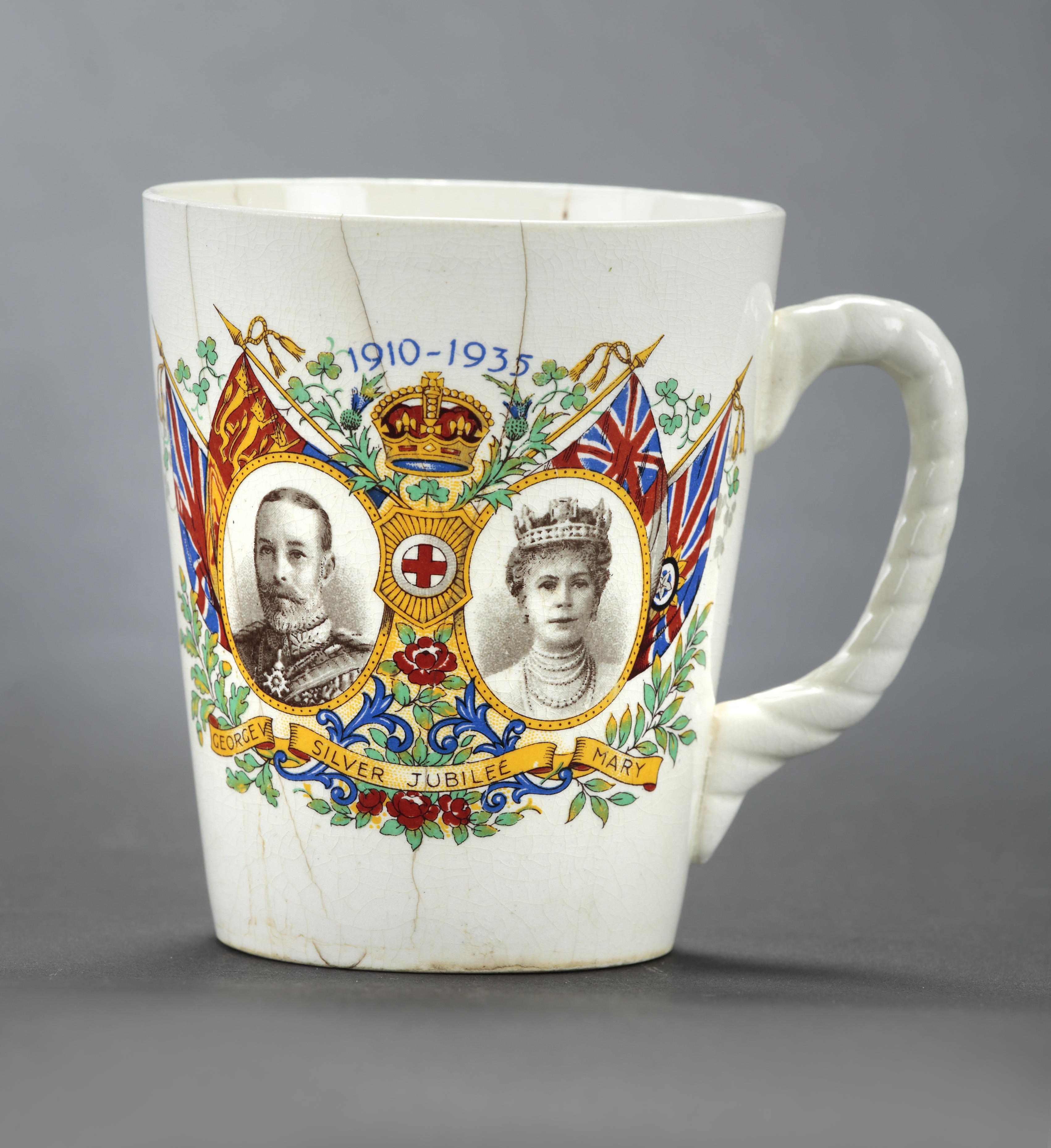 Semi-conical white ceramic mug with rope twist handle. Decorated on the front with oval sepia portraits of George V and Queen Mary in a polychrome surround of 4 flags, crown, national emblems and blue scrolls. Above in blue: