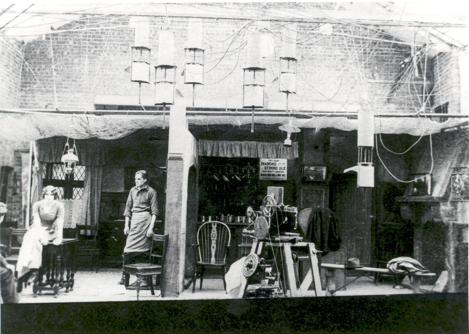 A film set at the Hepworth Studios comprising two rooms with a scene being enacted in the room on the left. The other appears to be a bar in a public house. Studio lighting etc visible in the foreground, 1912.