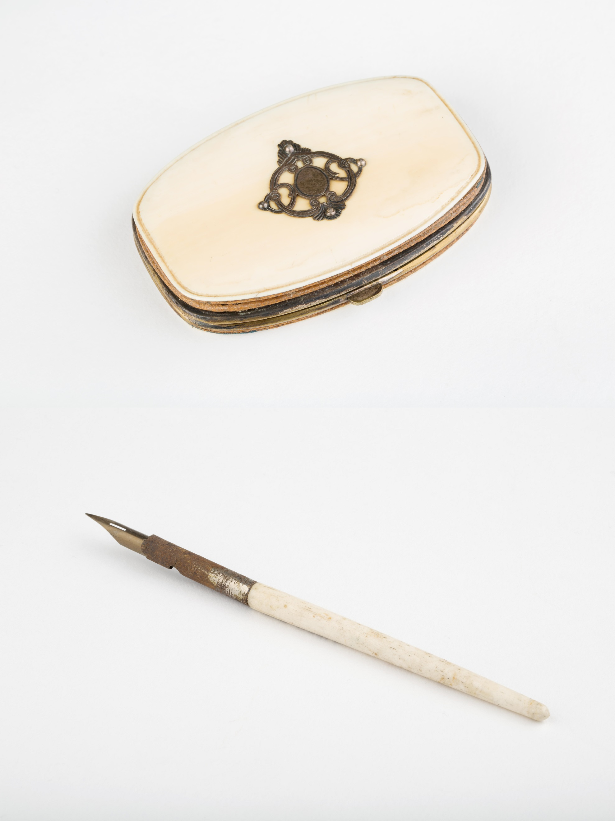 Top: Late Victorian lozenge-shaped small ivory purse. Inside is royal blue moire silk and a central purse section with a silver top and separate hinge. The purse has a silver design with four silver pins mounted on the front, to take initials. Bottom: a plain ivory pen holder.