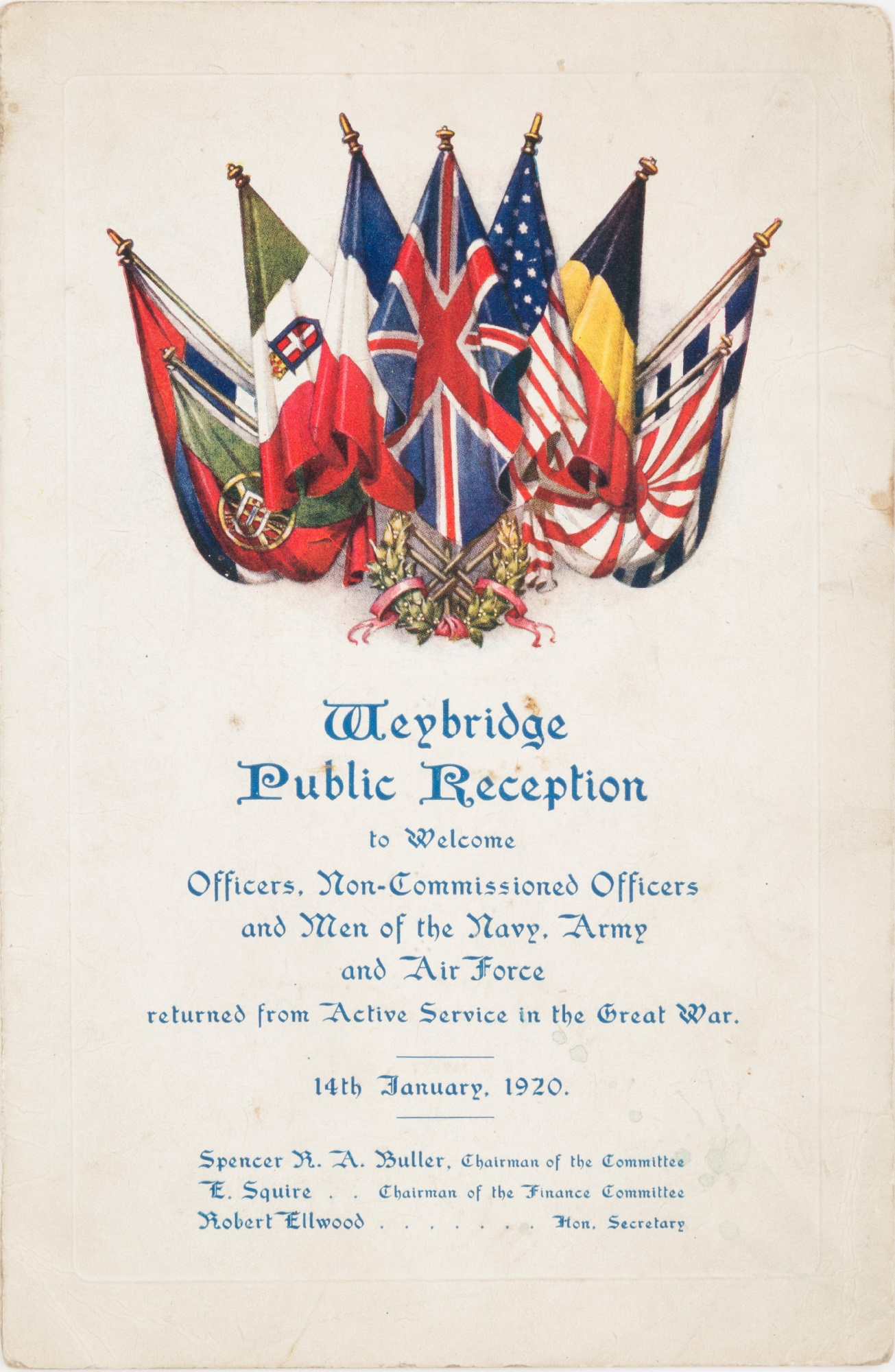 Programme for a Weybridge Public Reception dated 14th January 1914, to welcome men on active service in the Great War (1914-18). Nine flags are crossed at the top of the page, and details of the event are written in blue lettering on white card. Inside are details of the menu, programme, and the autographs collected.