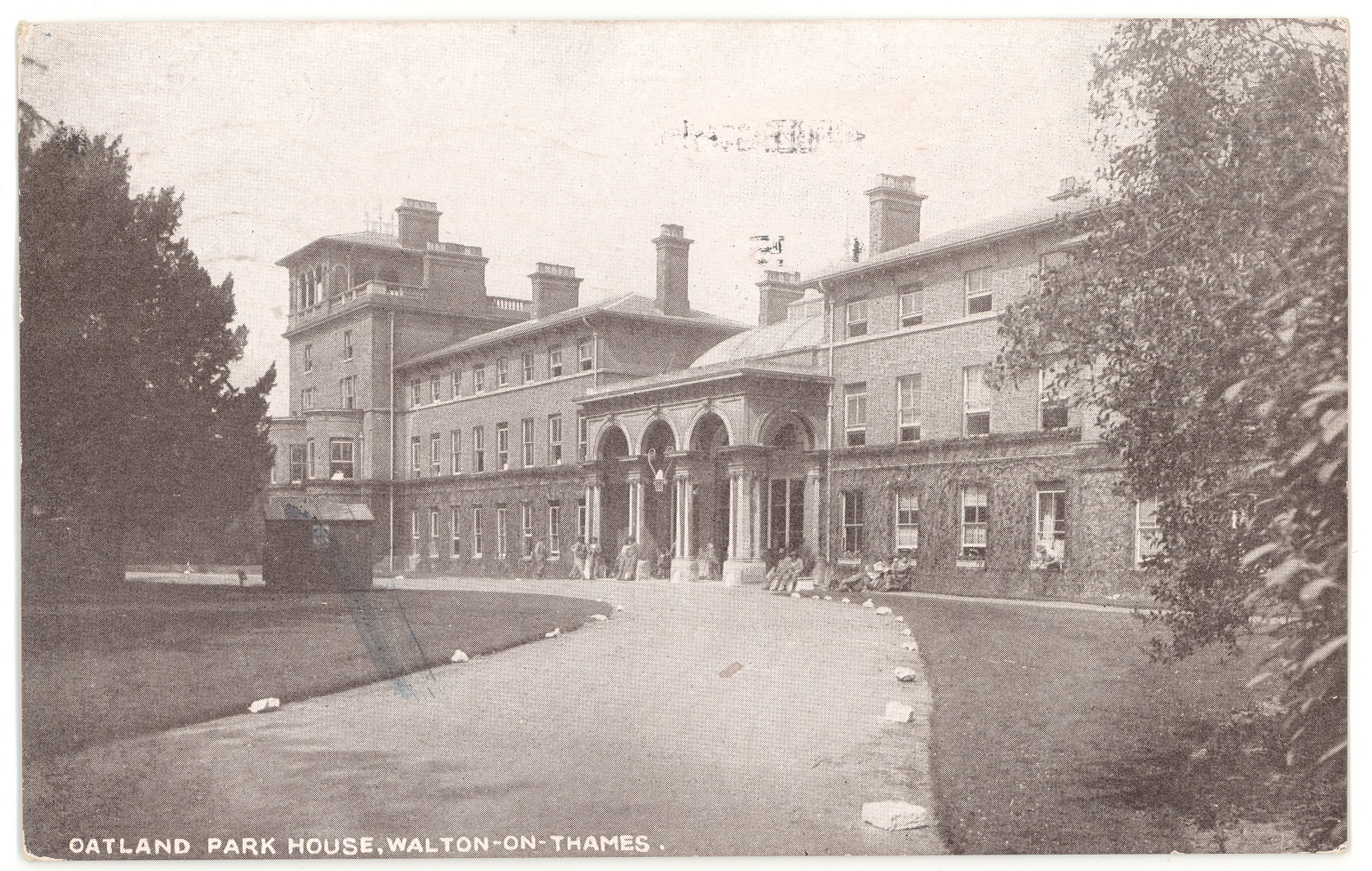 Black and white postcard of Oatlands Park Hotel, showing the curved drive to the porticoed entrance with New Zealand soldiers sitting and standing outside, October 1915.