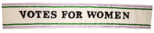 A reproduction of a 'Votes for Women!' sash in the Suffrage campaign colours of green, purple and white.