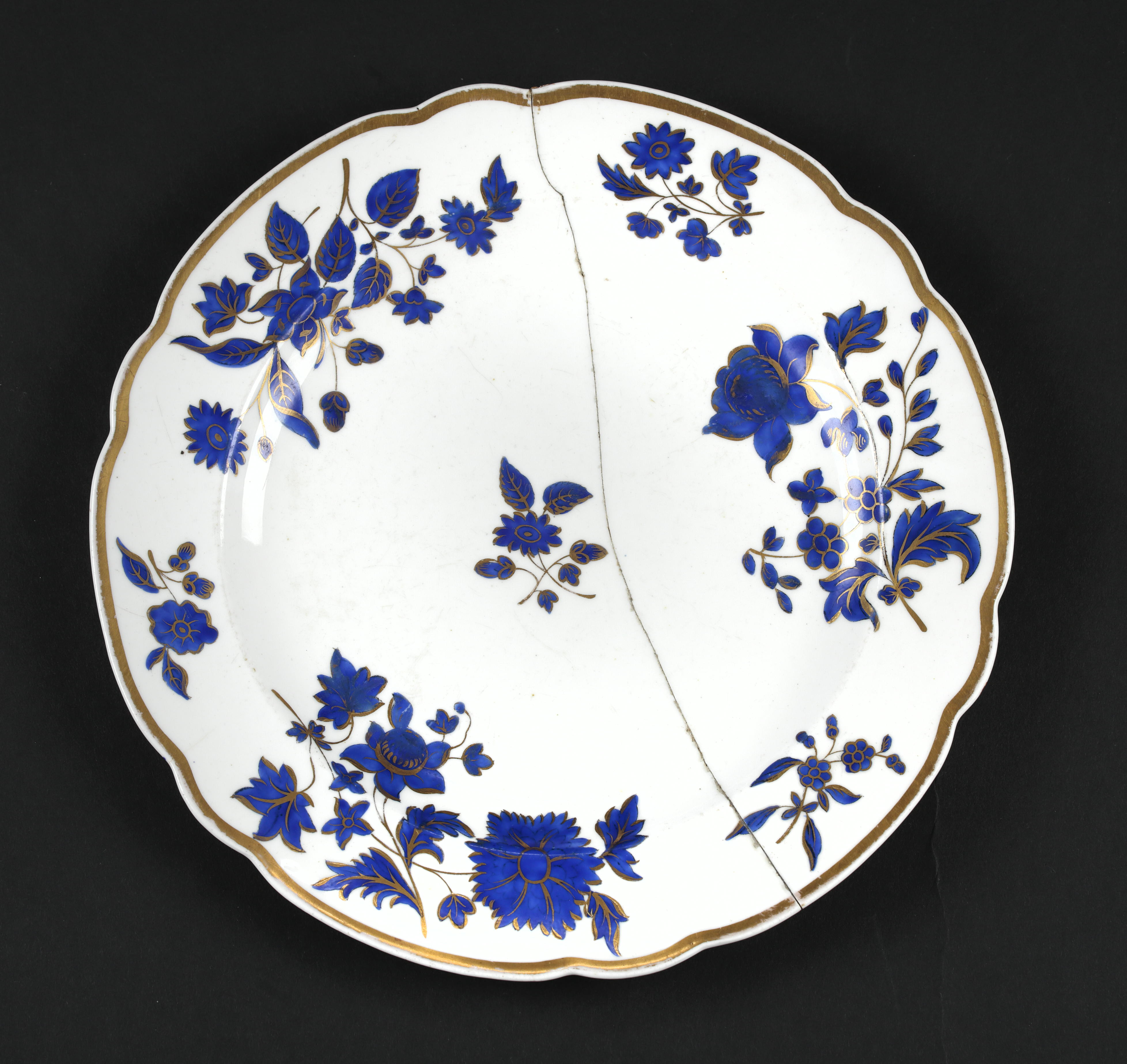 Dinner plate, part of a service used at Claremont during the time of the Duchess of Albany's residence there ( 1890's ). Circular with fluted edges, gold-painted outer rim, design of royal blue and gold flowers and leaves. On reverse side a circle of small flowers as a trade mark with
