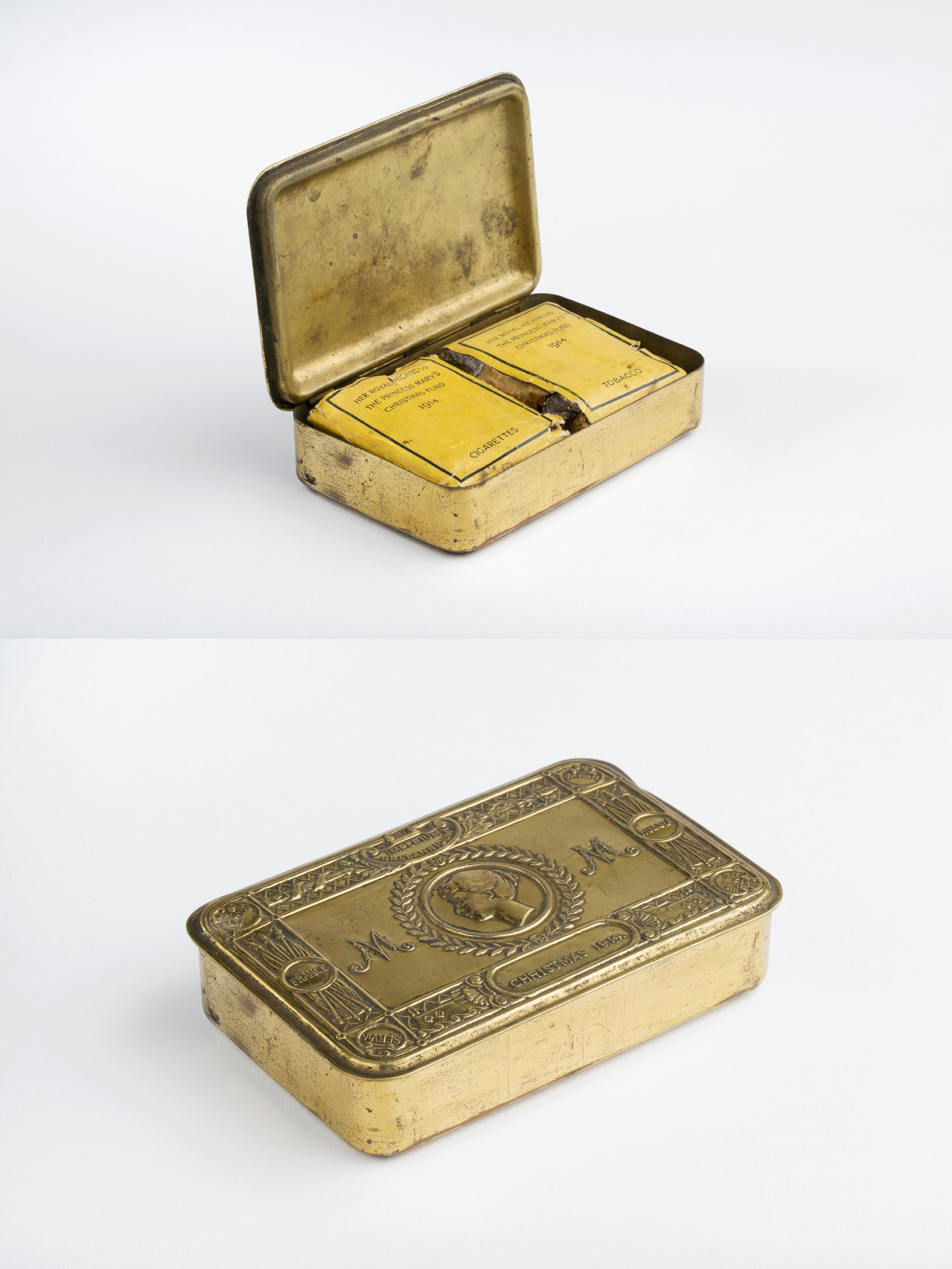 Brass-plated tin 'Princess Mary's Christmas Fund Tobacco tin containing the two original packets, one containing tobacco and one cigarettes. Top of tin central profile portrait of Princess Mary within a laurel wreath and 'M' embossed each side of circle.