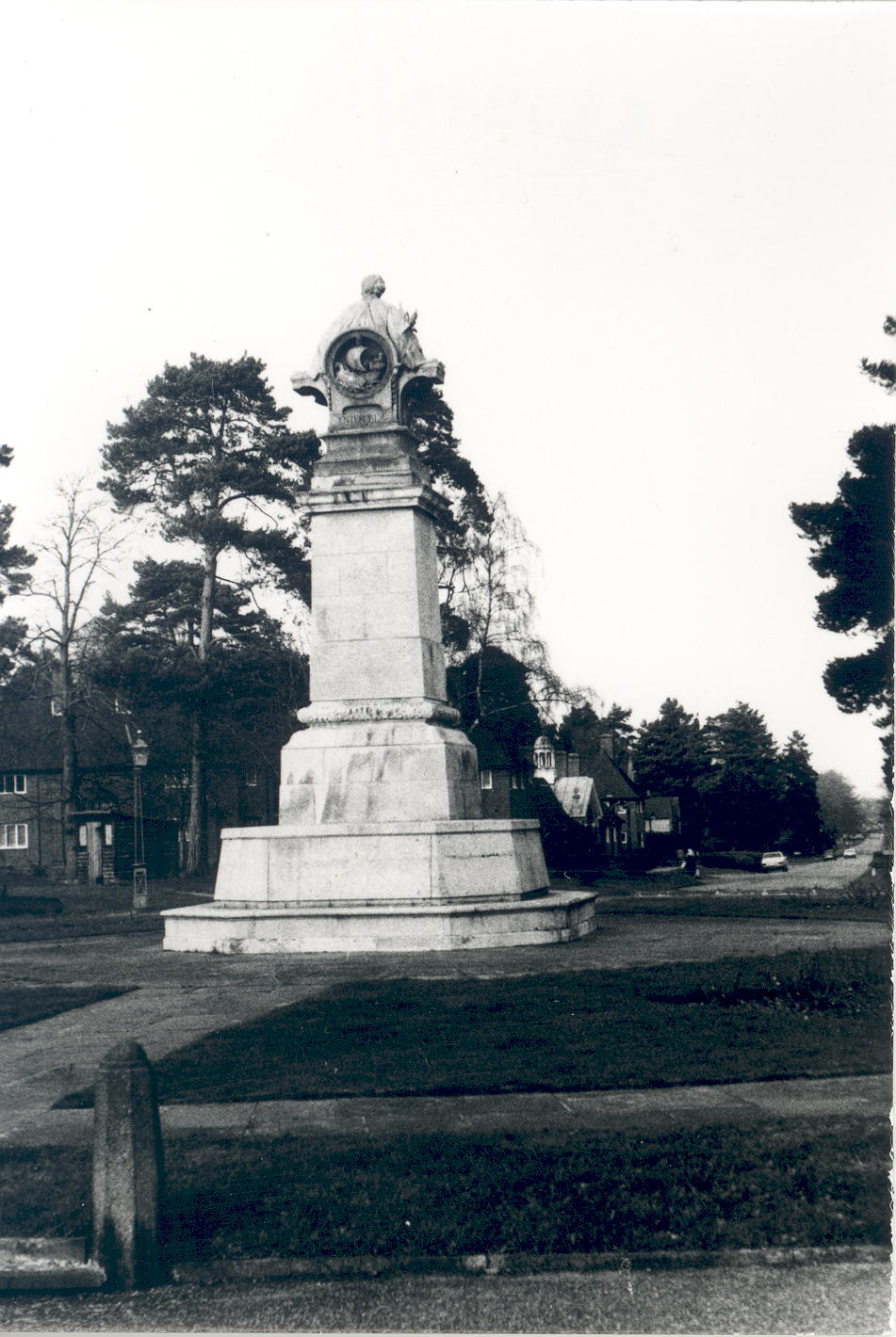Photograph of the Memorial to William Whiteley taken in 1983. The memorial stands in the centre of the octagon at Whiteley Village on a pavement with grass around.