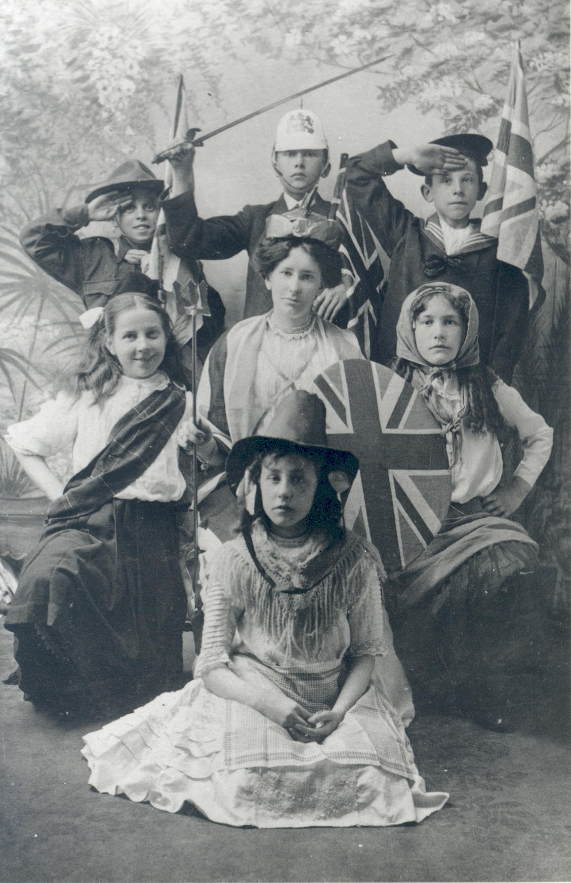 Black and white photograph copy of a postcard of woman and six children in fancy dress representing British Empire. Pre-First World War.