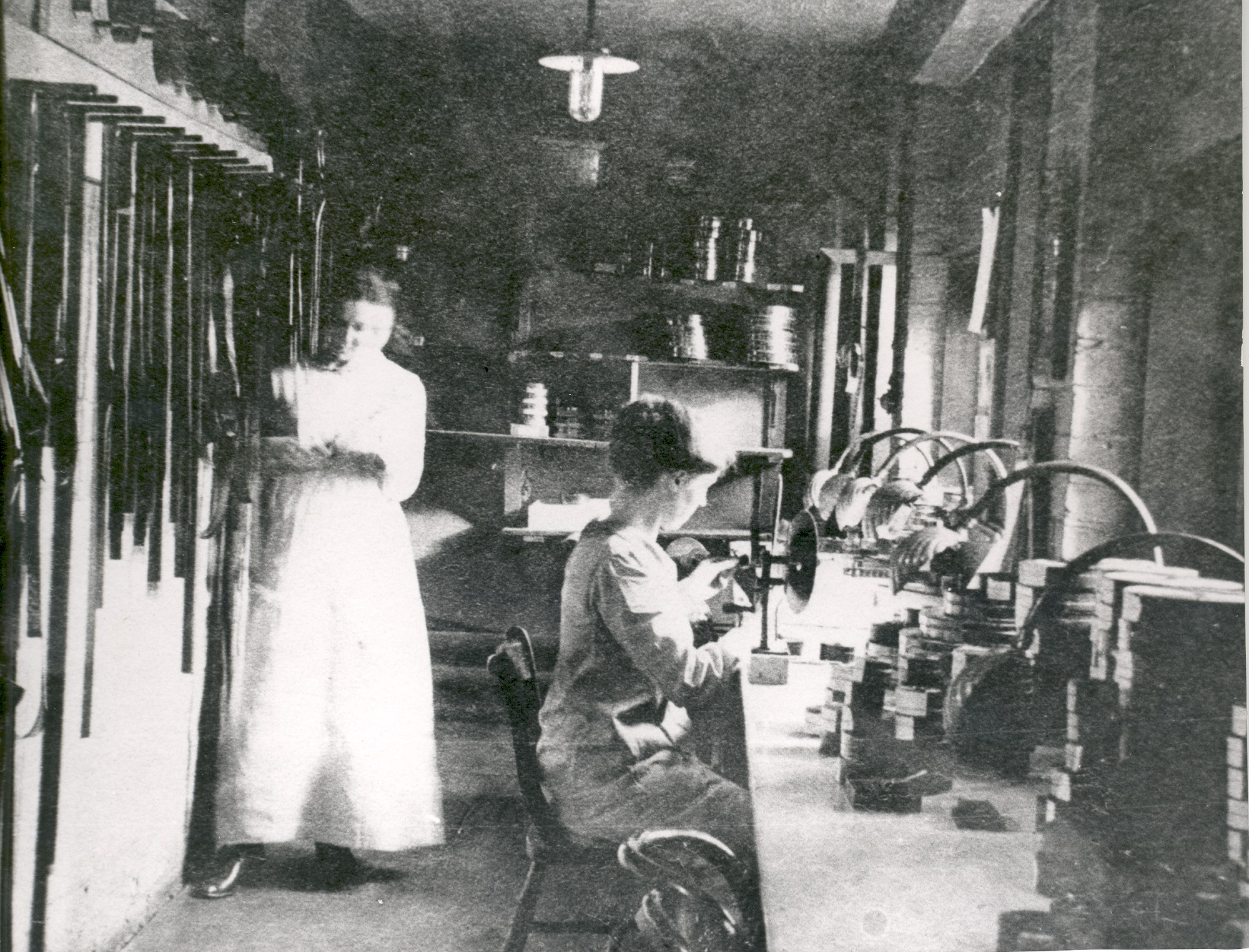 Two women cutting and editing film at the Hepworth Studios. Seated woman on right is Miss Gaiger. They are assembling in order sections of prints which have been printed blue (for night), salmon pink (romantic scenes), amber (sunlit scenes), red (fires or firelight), green (crime) and black and white for