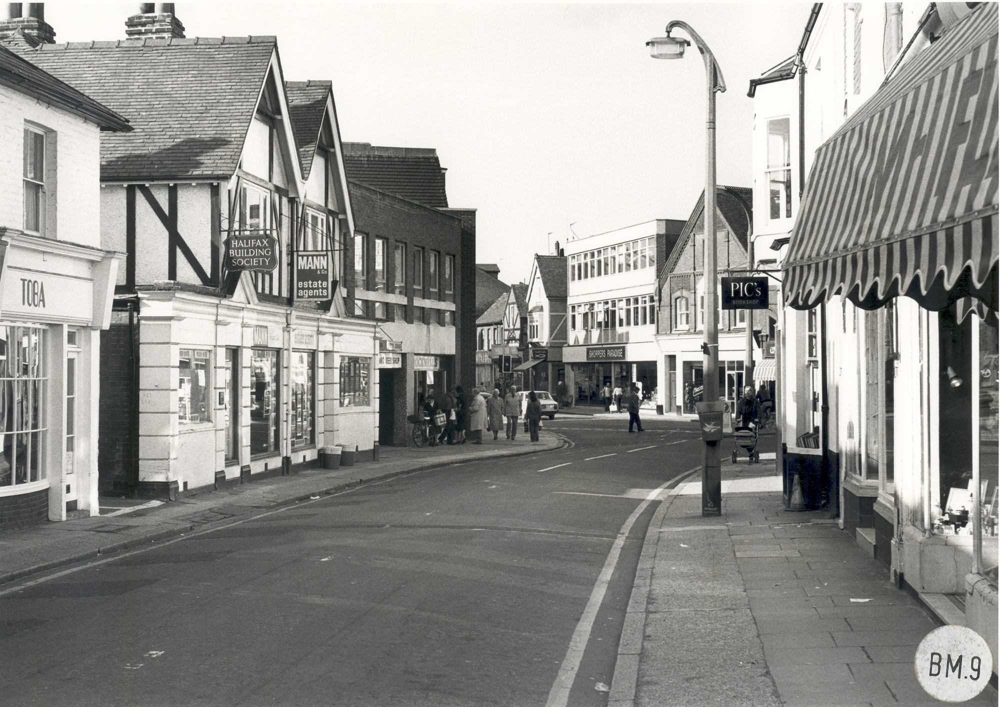 Black & white photograph of west end of Baker Street looking west, with Toba and Mann & Co. on left and part of Church Street in background including fish and chip shop, Shoppers Paradise & former Sainsbury's building, 1978.