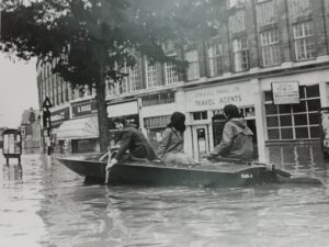 People in a boat in Walton Road, Molesey, in the 1968 floods. Copyright H Storey.