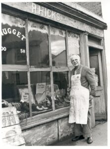 Mr Hicks standing outside his cobblers shop in Bridge Road, East Molesey, 1976.