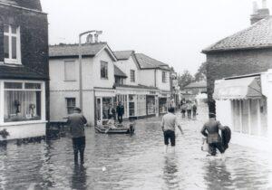 Pedestrians in flood water in the Village High Street, Thames Ditton, September 1968.