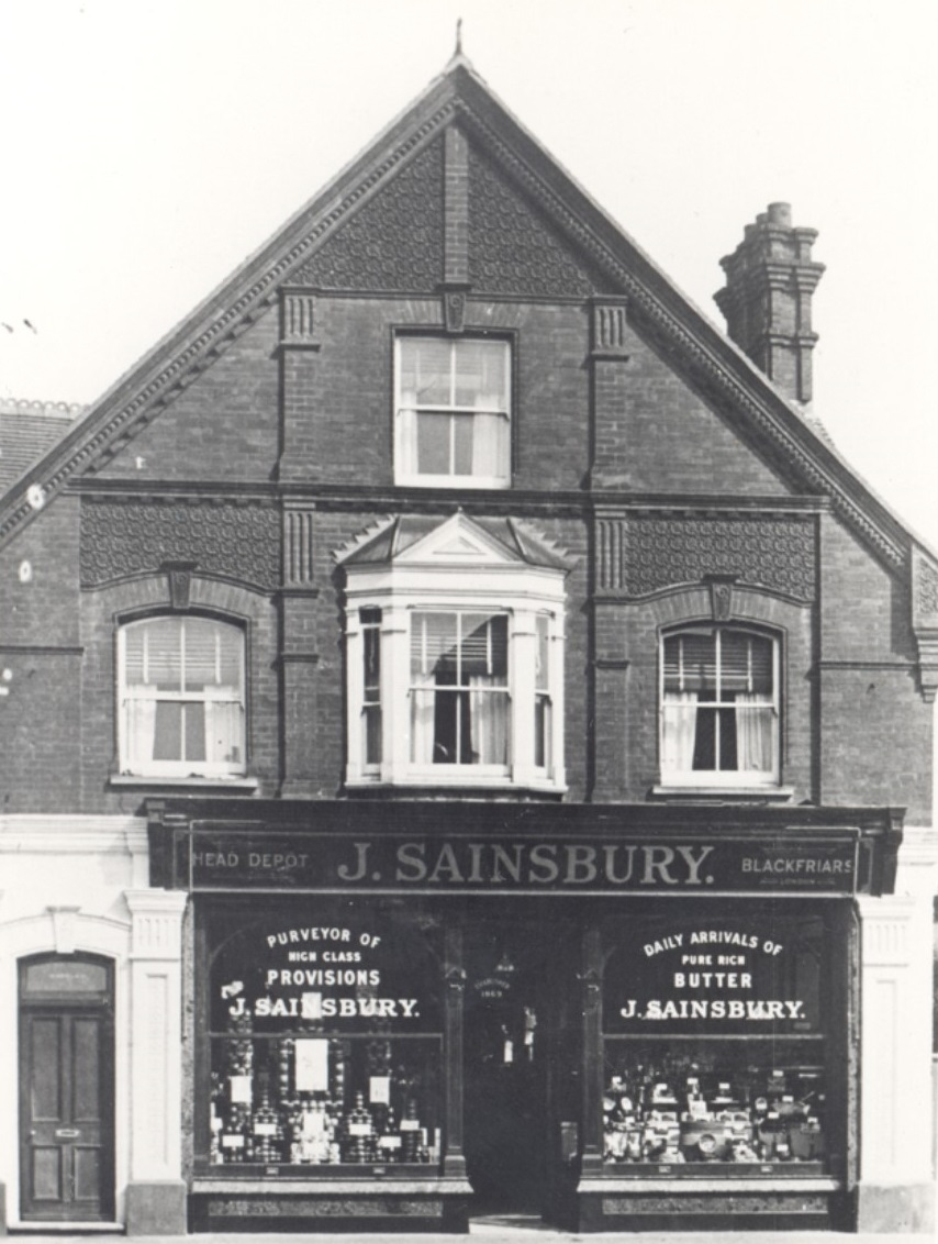 Photograph of Sainsbury's shop in Church Street, Weybridge, showing pointed gable, windows over shop front, shop front and front door of flat above. Photograph taken about 1932, when Sainsbury's first opened in this building.
