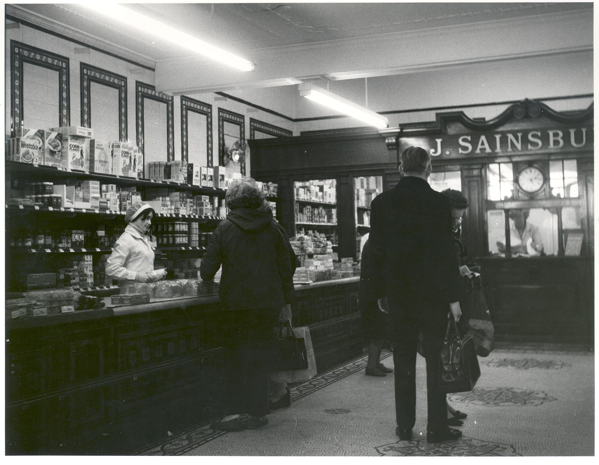 The inside of J. Sainsbury's shop, Weybridge c.1970s, showing an assistant behind the left counter and a group of 5 people standing beside the counter. The cash office can be seen on the right.