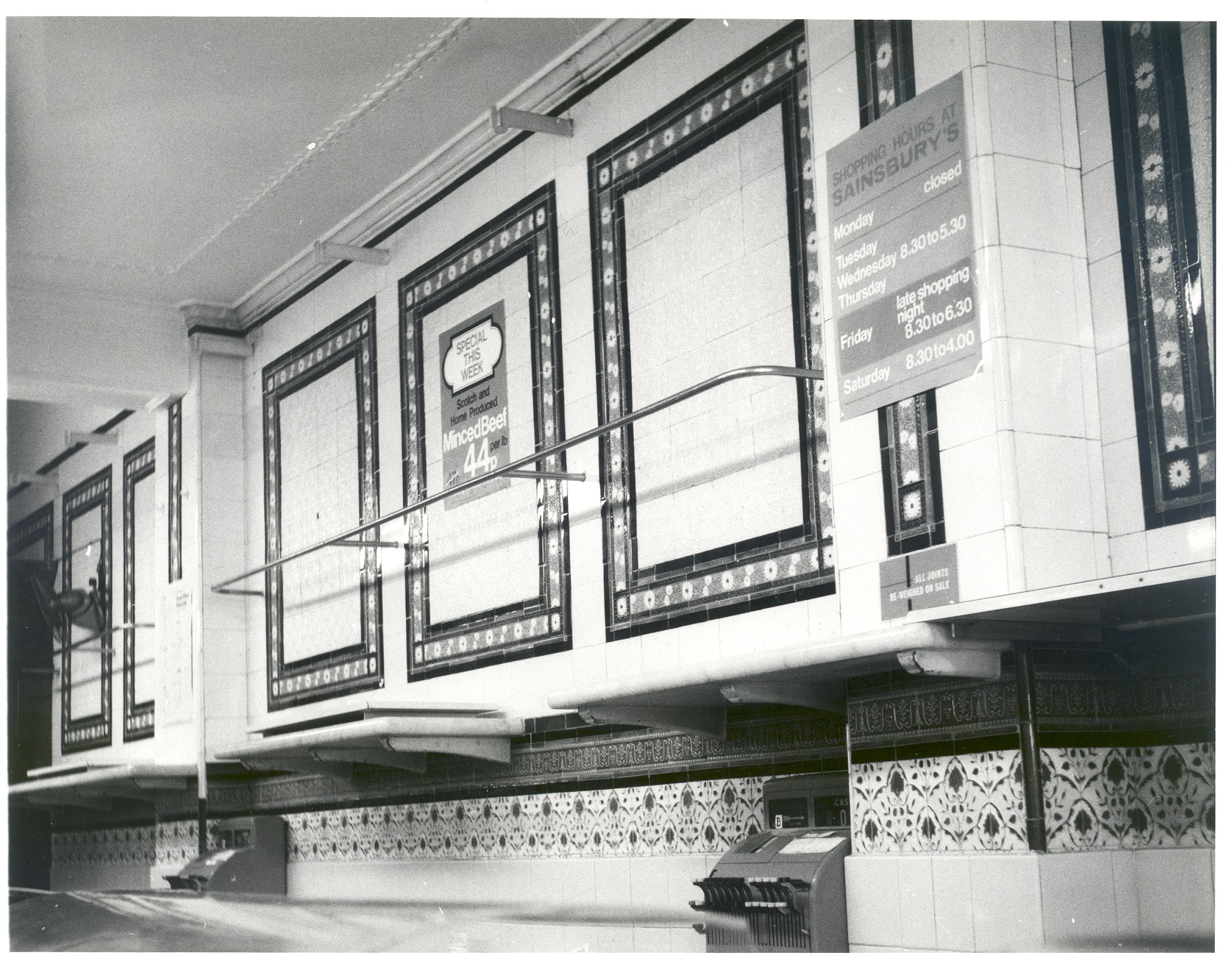 Photograph of J. Sainsbury's shop in Weybridge c.1970s, showing cleared shelves and counters with 2 cash registers at the back.