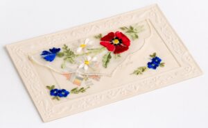 Embroidered Christmas card with a poppy, daisies and cornflowers embroidered on the front. Inside the pocket is a card with 'Glorieux Souvenir 1914-15' and 'I'm thinking of you' printed on it. This was sent from a soldier during the Great War, and demonstrates the prevalence of the Poppy in imagery at the time.