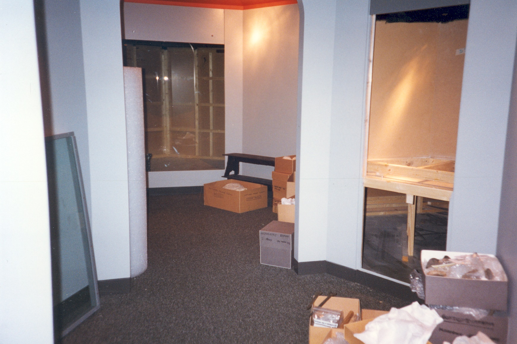 The interior of Elmbridge Museum during refurbishment, May to December 1996, showing empty Pre-historic Elmbridge and Oatlands Palace display cases with boxed objects on the floor.