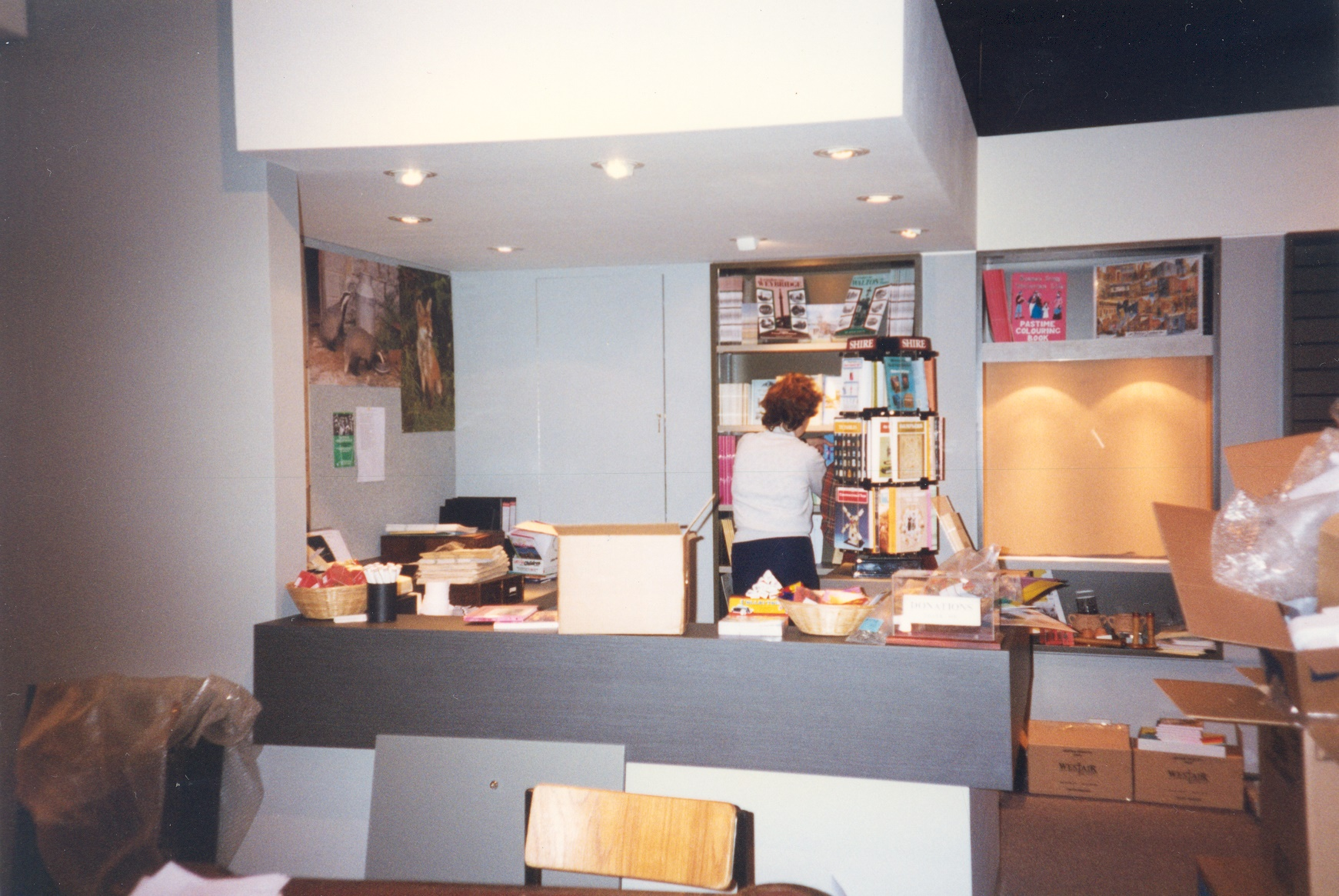 A person stocking the shelves of the Elmbridge Museum reception desk and shop, during Museum refurbishment, May to December 1996.