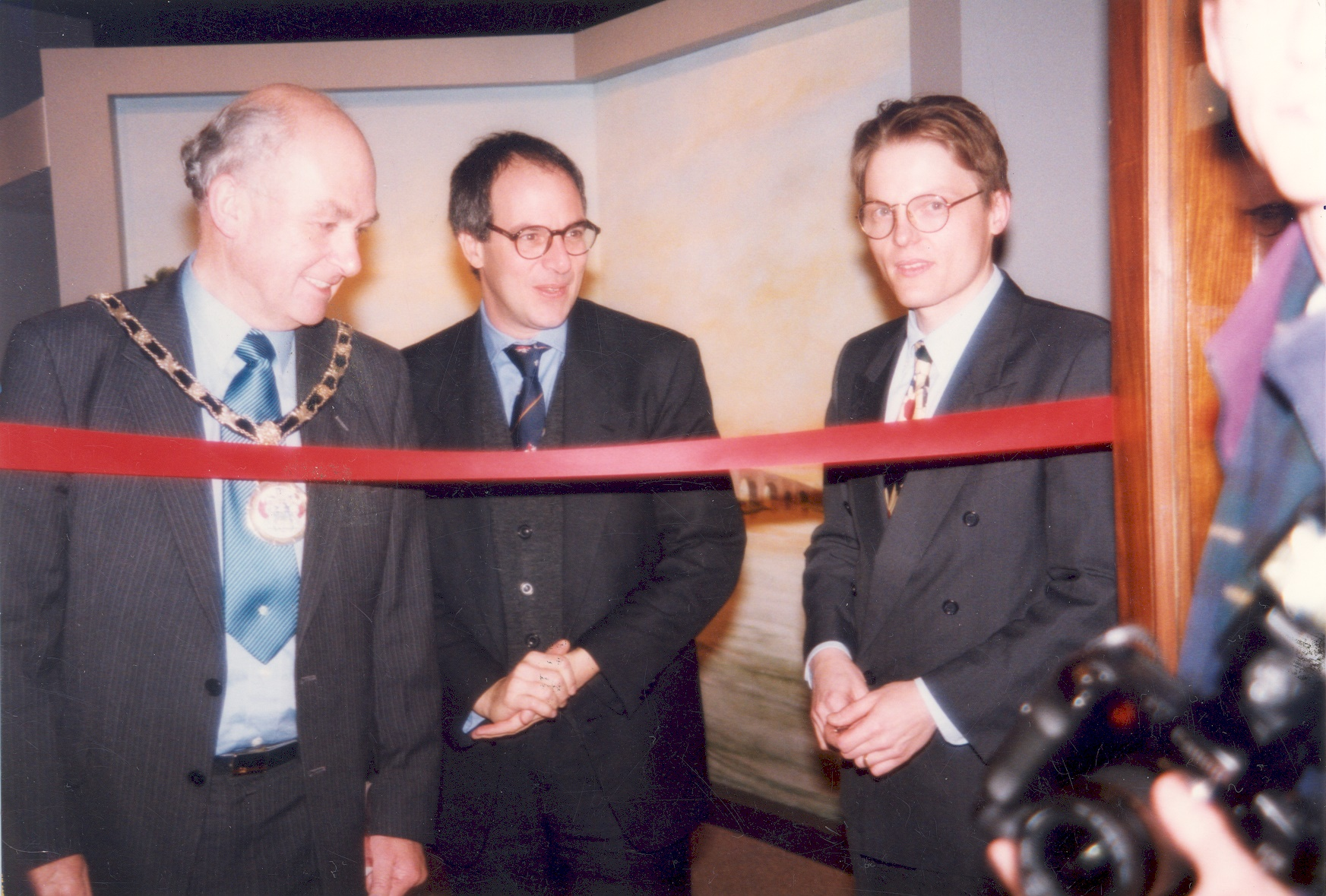 The Mayor of Elmbridge, Loyd Grossman and Neil White, Museum Manager, at the opening of the refurbished Elmbridge Museum on 10th December 1996, with the red ribbon across the Museum entrance, and press photographers in the vestibule.