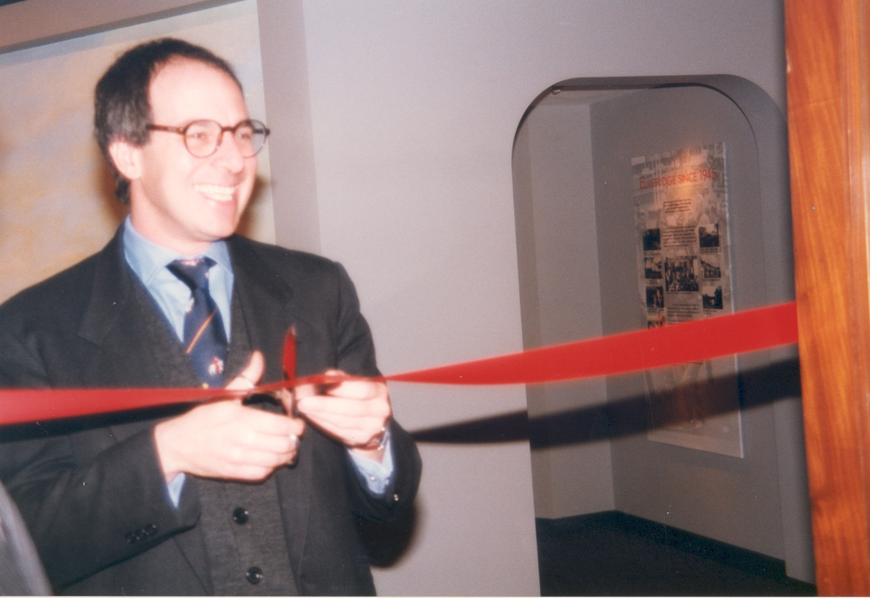 The re-opening of Elmbridge Museum on 10th December 1996 by Loyd Grossman, showing him cutting the ribbon across the Museum entrance, as seen from the Vestibule.